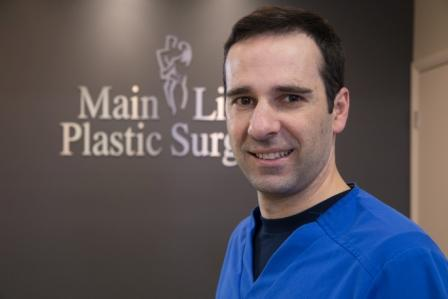 breast surgeon Dr. Raymond Jean in front of Main Line Plastic Surgery sign