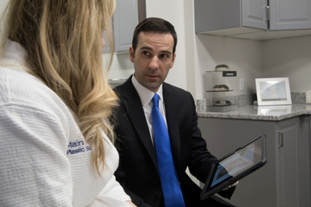 board-certified plastic surgeon Dr. Raymond Jean consulting with patient