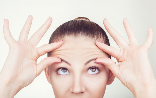 woman drawing attention to her forehead wrinkles prior to BOTOX treatment