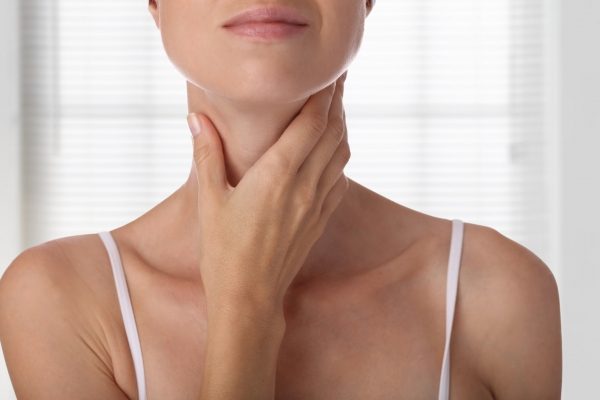 woman holding her neck after a neck lift procedure