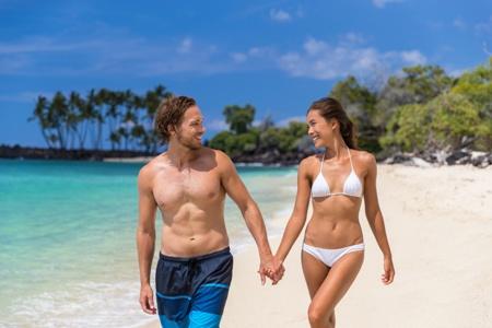 couple in swimwear walking hand-in-hand on the beach