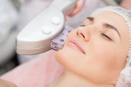 med spa technician performing laser skin treatment on a woman's cheek