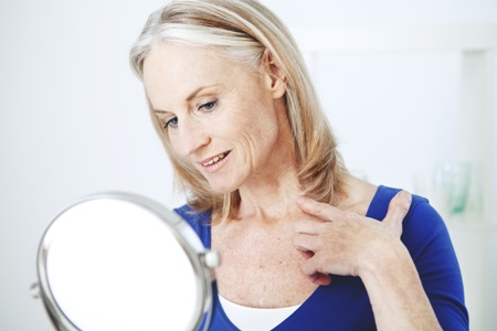 older woman looking at sagging neck skin in the mirror