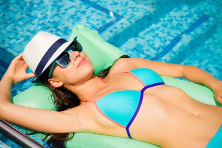 woman in bikini relaxing on floating mattress at the pool