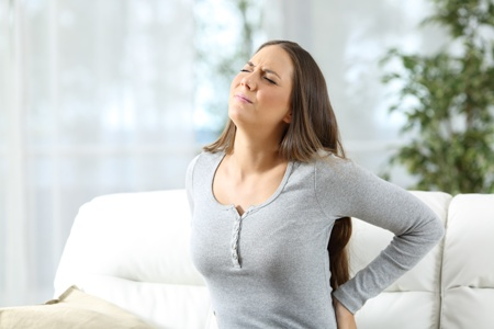 woman with back pain wincing
