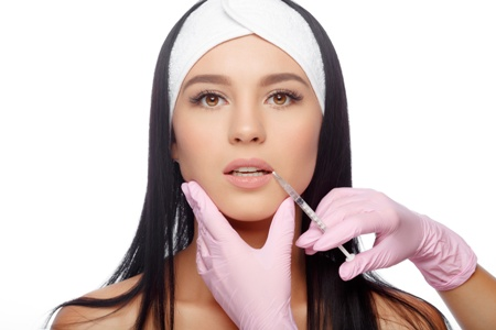 young woman getting lip filler injection