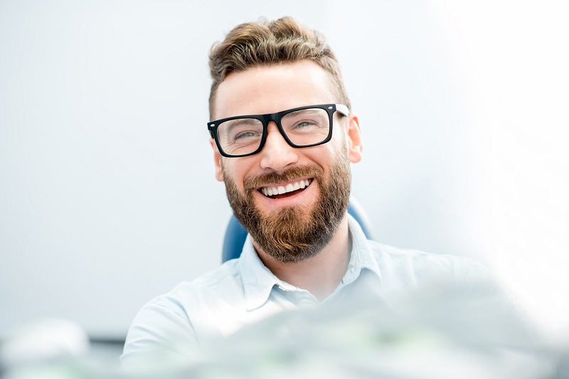 Bearded man smiling in a dentist's chair during his initial consultation