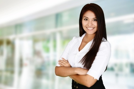 smiling woman standing in office with her arms folded