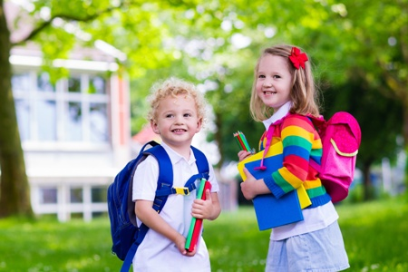 smiling boy and girl carrying school supplies