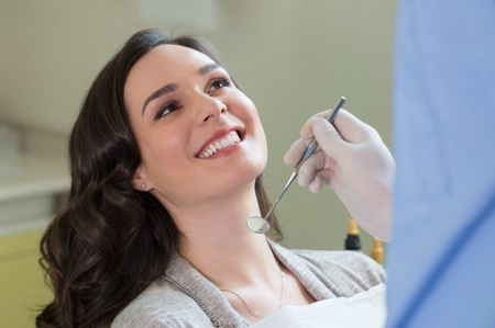 woman smiling at dentist during exam