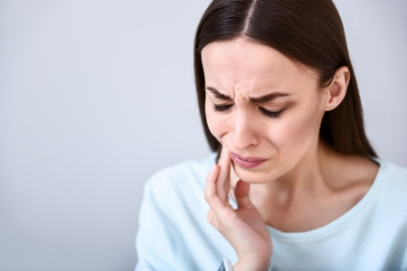 woman with toothache grimacing while holding her face