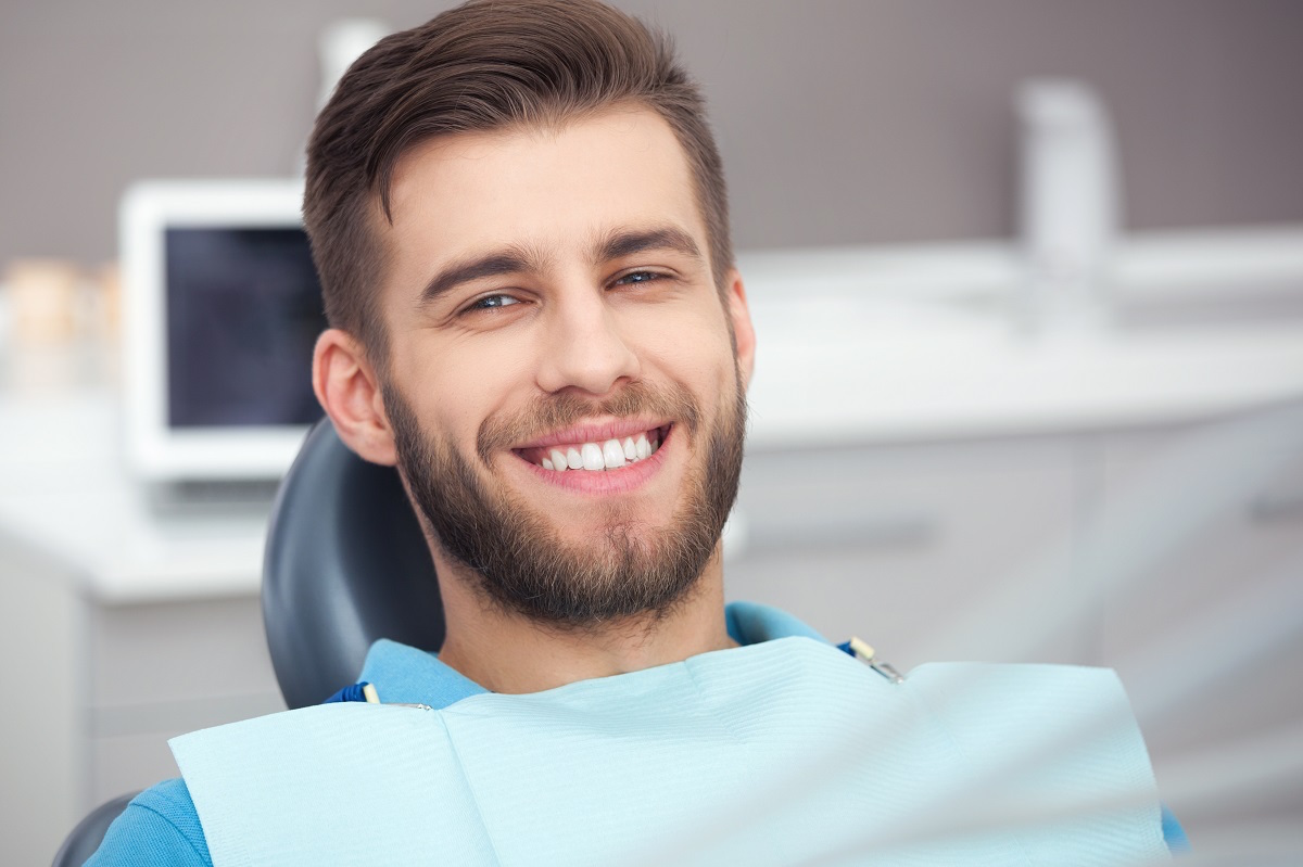 Man with nice teeth smiling in a dental chair after having dental crowns or porcelain veneers placed