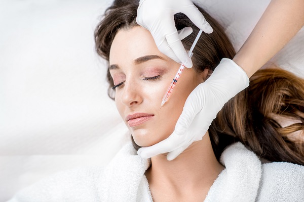 Woman receiving injectable dermal fillers and wrinkle relaxers