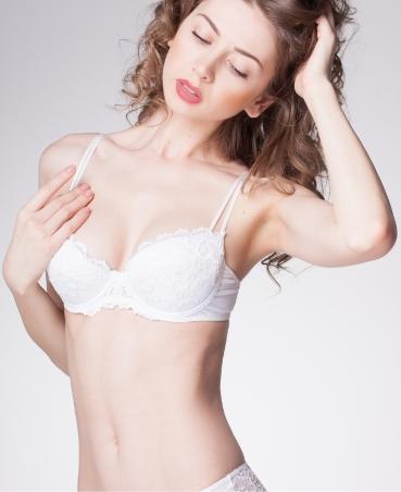 Beautiful woman touching her bra strap