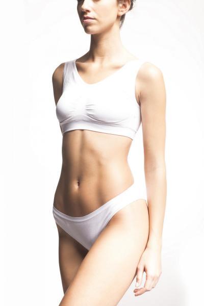 woman in sports bra nad underwear after undergoing Emsculpt treatment