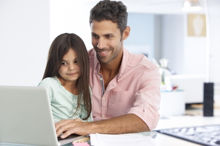 dad and daughter using laptop computer