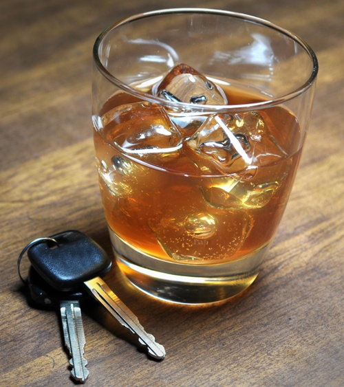 A glass of alcohol with ice and a pair of carkeys sitting beside it to sybolize drinking and driving.