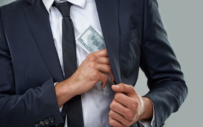 man in a suit putting stolen money into his inside jacket pocket