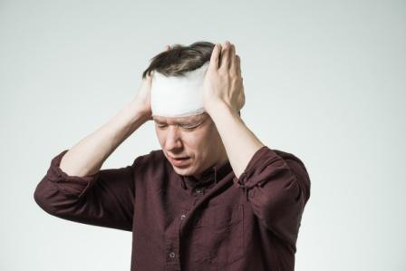 pained man grabbing his bandaged head