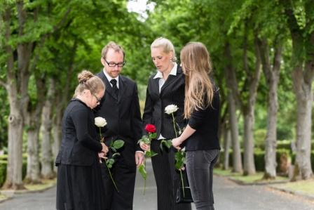 grieving family holding flowers