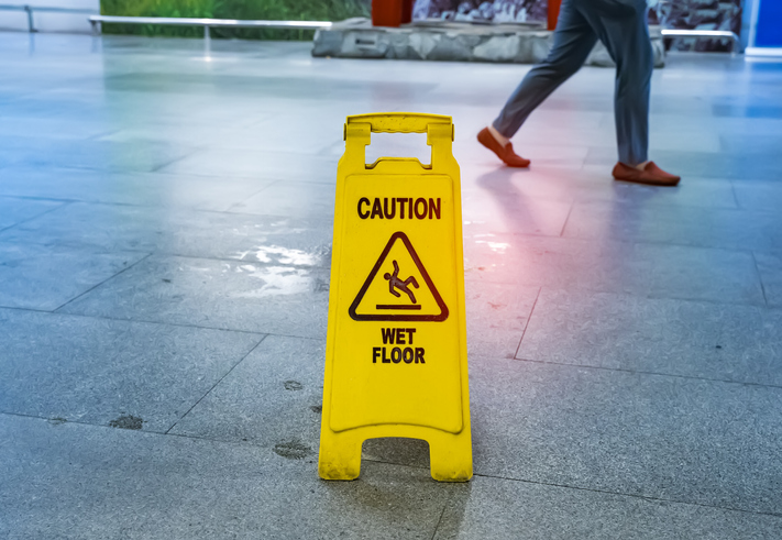 A picture of a wet floor sign next to a puddle of water.