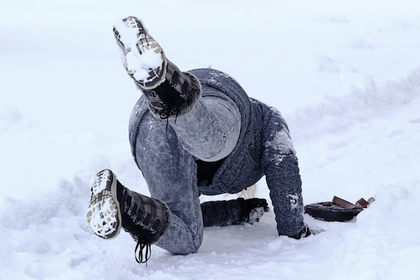 person slips and falls on a snowy walkway