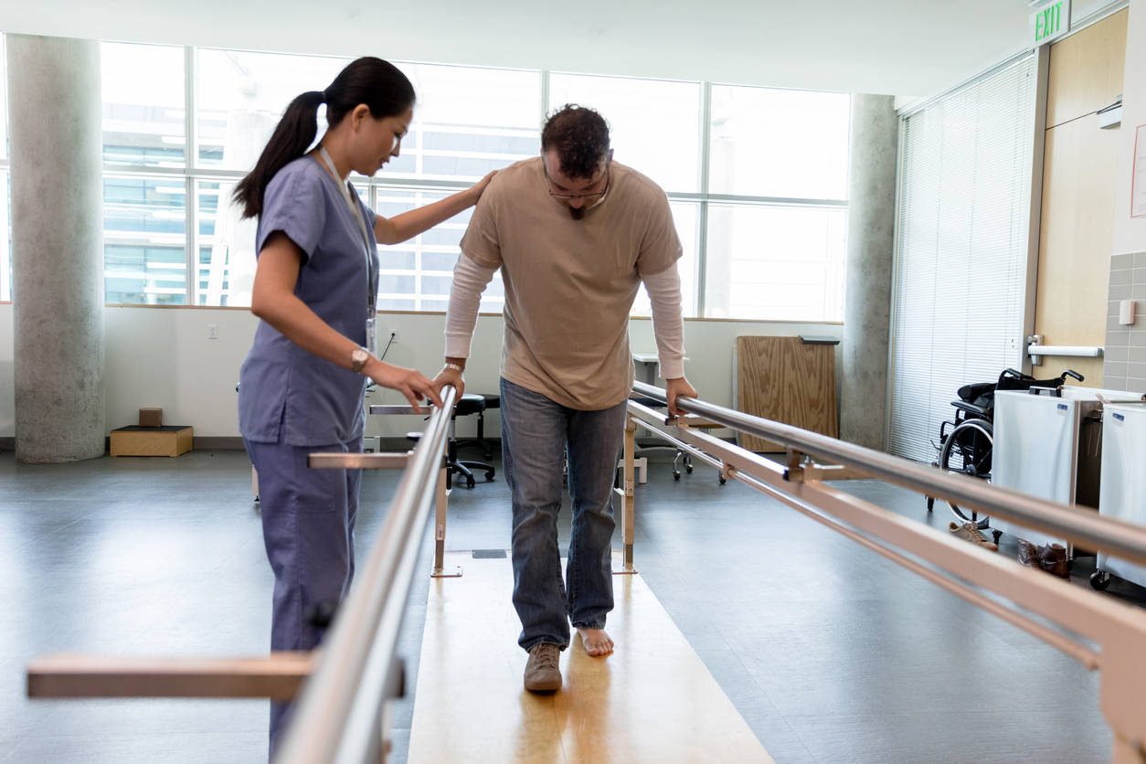 A rehabilitation specialist assists an injured man with an exercise