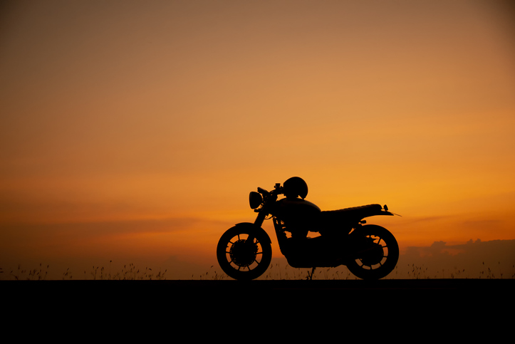 A silhouette of a motorcycle in front of the horizon.