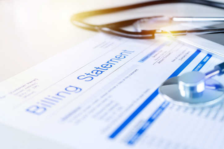 A close up of a medical bill with a stethoscope laying nearby on the table