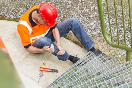 injured worker holding leg near metal steps