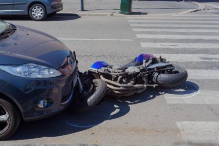 motorcycle crashed under front of car