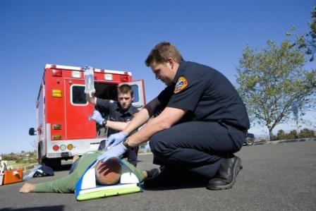 paramedics assisting man injured in the road