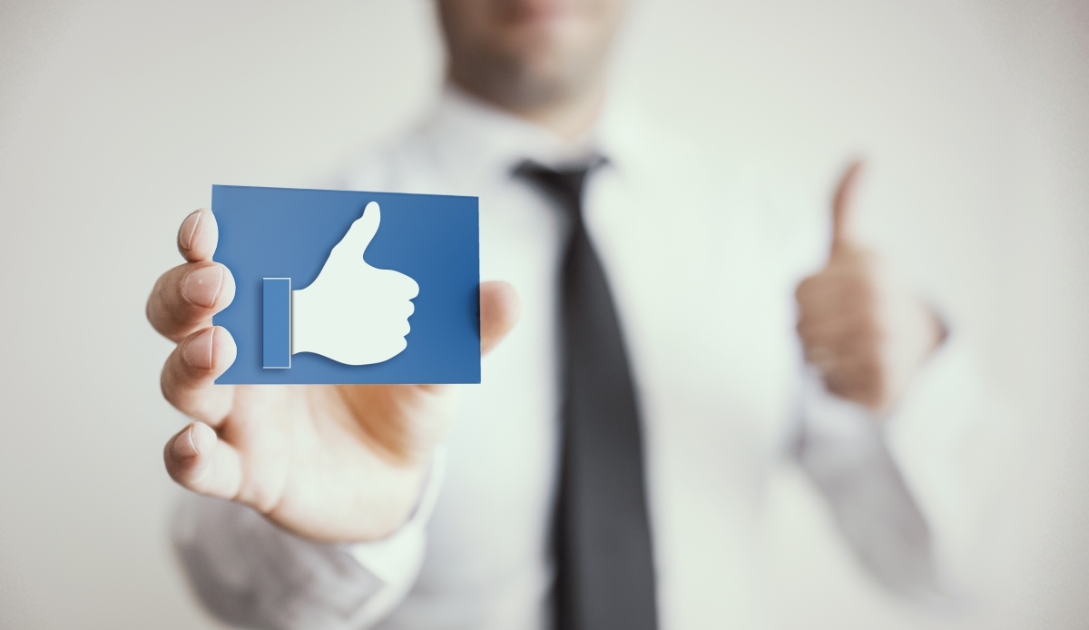 businessman holding Facebook 'thumbs up' icon