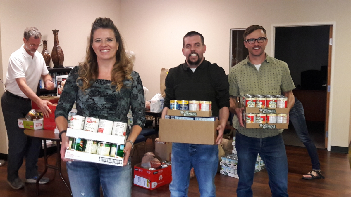 Page 1 Solutions team members load Thanksgiving food drive contributions for The Action Center