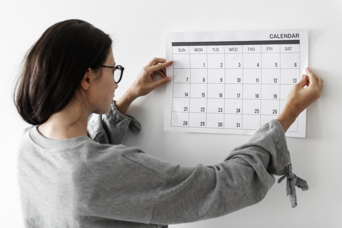 woman pinning a calendar on the wall
