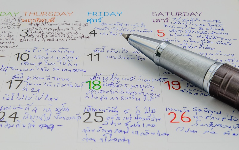 pen resting on desk calendar with busy appointment schedule