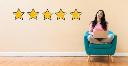 young woman writing 5-star review on your laptop