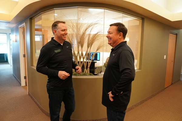 our dentists, Dr. Scott Peppler and Dr. Joseph O'Leary, talking at the front desk of Meadows Dental Group