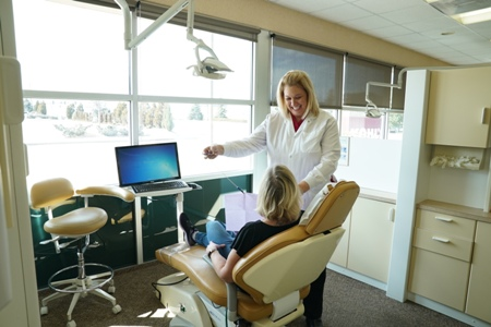 hygienist at Meadows Dental Group placing bib on patient