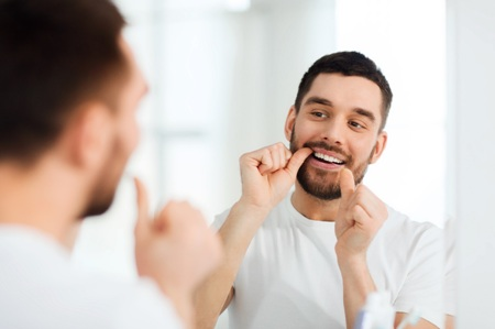 man looking in the mirror while flossing