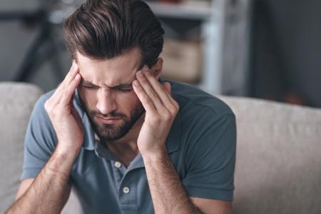 man with TMJ headache rubbing his temples