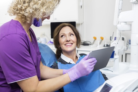 dentist reviewing veneers treatment with patient on tablet device