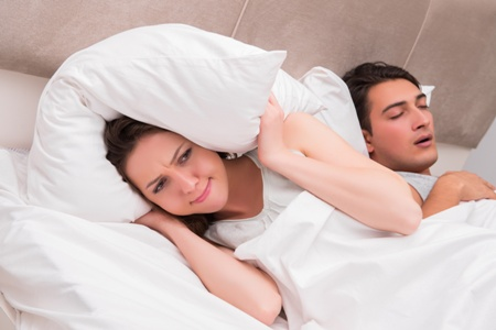 woman putting pillow over her head to drown out snoring man