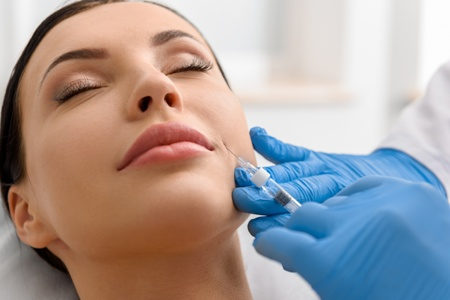 woman getting injection in lower face for TMJ pain