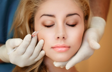 young woman closing her eyes while getting BOTOX injection