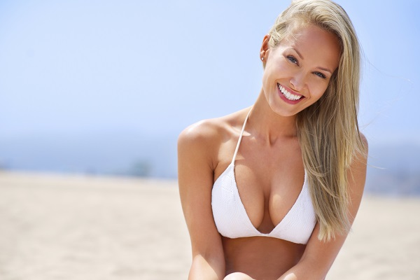 woman in white bikini after breast augmentation surgery