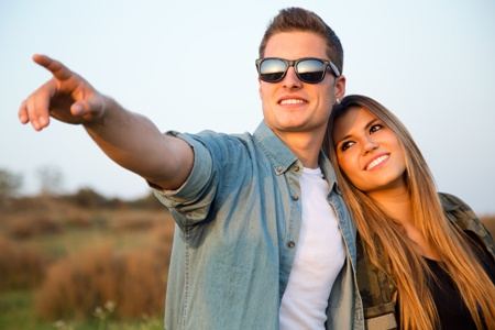 man pointing to horizon in field with girlfriend by his side