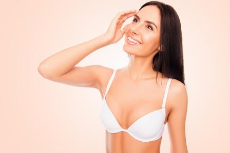 smiling woman in white bra | Plastic Surgeons of Lexington
