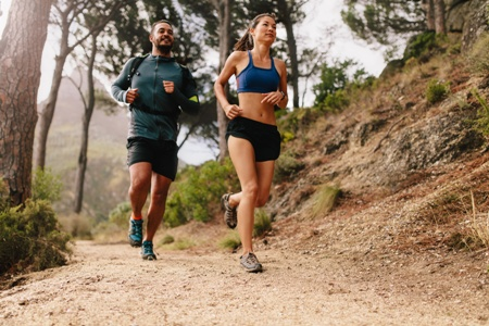 athletic couple jogging on mountain trail