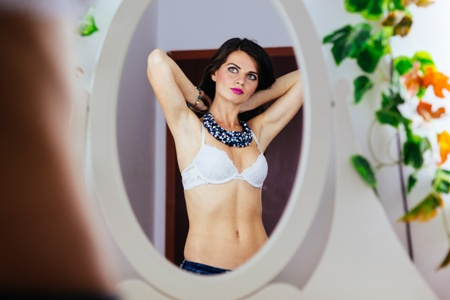 woman in bra looking in the mirror